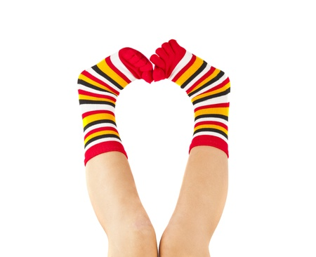 female legs in colorful striped socks isolated on white photo
