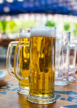 Two beer mugs close-up on wooden table photo