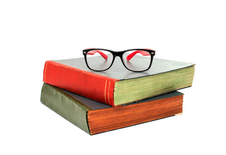 book with glasses on white background