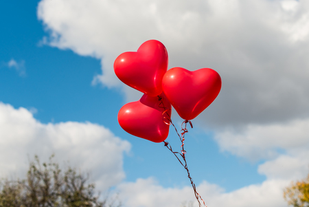 abstract heart background: red heart balloons outdoors