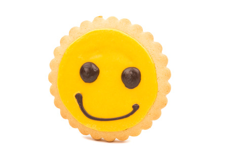 smilie: Yellow Smiley biscuit on a white background. Stock Photo