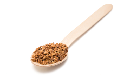 kasha: Buckwheat in a wooden spoon isolated on white background