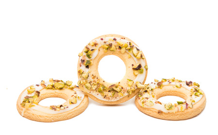 Ring biscuits with pistachios on a white background