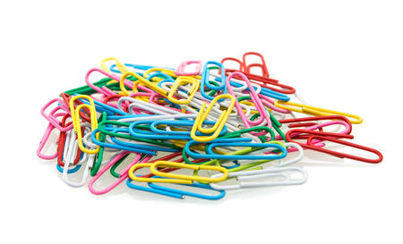 A pile of colorful paperclips sit on a white background