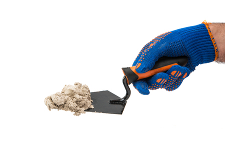 trowel with mortar in the hand of the builder isolated on a white background