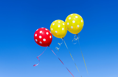 Balloons of different colors against the blue sky