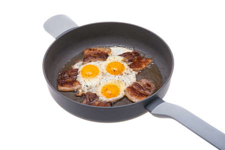 fried eggs with bacon in a frying pan isolated on a white background.