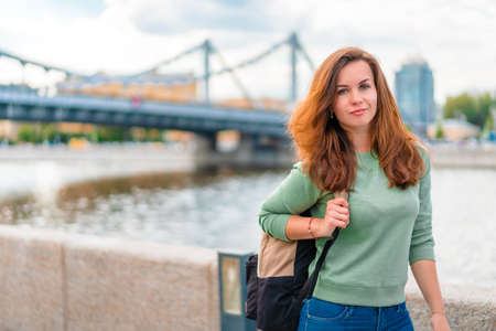 A young brunette woman with a backpack walks along the embankment in Moscow