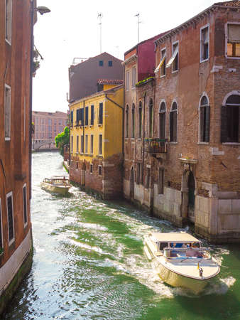 Cozy street in Venice with canals and gondolas, the tourist season in Italy