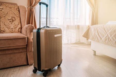 Travel suitcase stands in a white clean hotel room with light from the window, relaxing time, holiday, weekend and traveling concept.