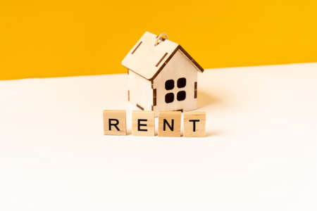 The concept of rental housing, rental real estate in the form of a wooden toy house on a white table. Words from wooden blocks 版權商用圖片