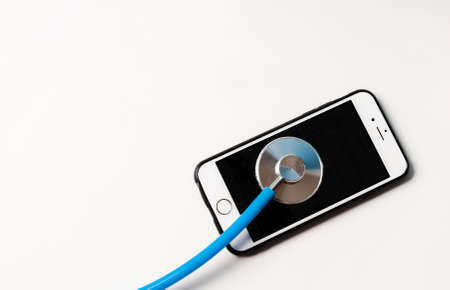 Digital tablet and smartphone being diagnosed with a stethoscope on white background. Repair and Service concept. 免版税图像