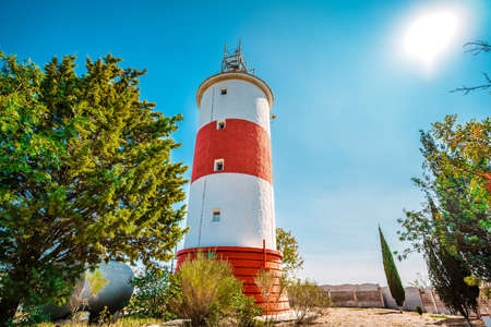Lighthouse with red stripes on a background of blue sky, beautiful landscape 版權商用圖片