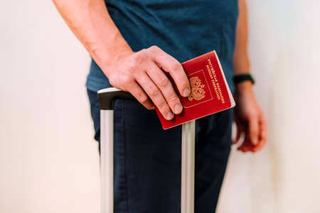 A man holds a Russian passport and the handle of a travel suitcase