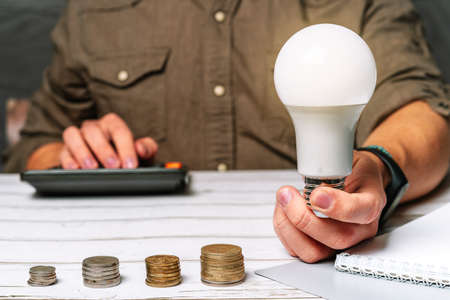 Business man hand holding a light bulb using a calculator to calculate cash flow. The idea of saving energy and accounting Finance in the office concept