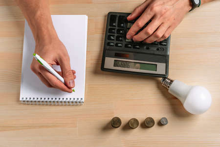 A glowing light bulb lies on the table next to a calculator and a stack of coins. The idea of saving energy and accounting Finance