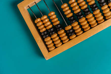 Top view of vintage abacus and modern calculator on a green background, the concept of finance and mathematical calculations
