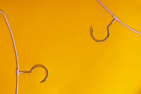 Clothes hangers are on a yellow background, top view. The concept of fashion Stockfoto