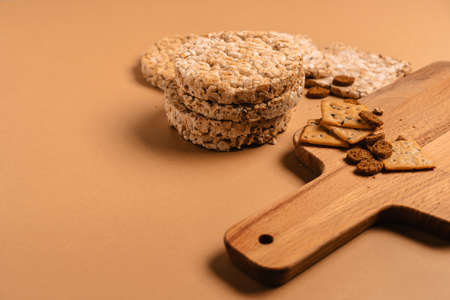 Various types of healthy whole grain crispbreads and cookies on a brown cozy background on a wooden Board.
