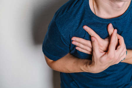 The man feels pain in the area of the heart and holds his chest with two hands. The concept of reflux disease or diseases of the heart system. Space for text on a white background