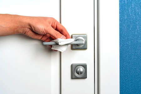 Hand wipes the door handle with an antibacterial disinfecting cloth, prevention of coronavirus Stockfoto