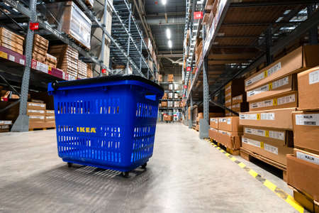 Large warehouse interior with rows of shelves and carts in IKEA