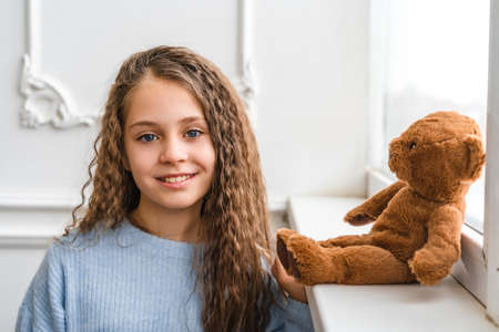 A beautiful little girl looks into the camera, a toy bear is sitting on the window