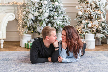 Attractive happy couple man and woman on Christmas day standing in front of the decorated tree smiling lovingly into each others eyes Standard-Bild
