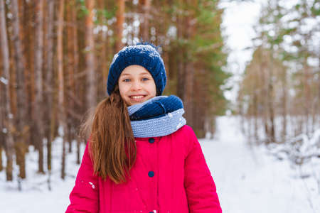 Portrait of a little happy girl in winter in a snow-covered hat who walks in the winter forest