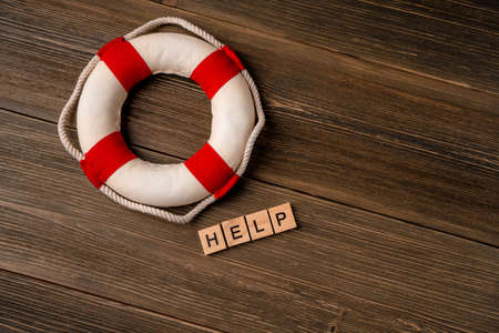 """A lifebuoy next to the letters """"help"""" made of wooden blocks on a wooden table. Support concept"""
