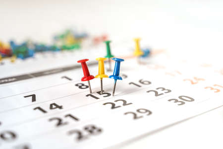 Lots of colorful pins on the calendar close-up with selective focus. The concept of planning.