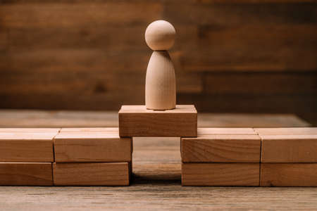 Wooden figurines of people stand on the planks of the bridge opening made of wooden blocks as a concept of risks in business and strategy