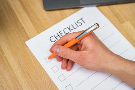A man's hand holds a pen and writes a check list with checkboxes, a wooden table. Time management concept