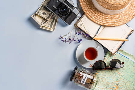 Top view of travel accessories when planning a trip: a camera, a notebook, a cup of tea. Space for text and a jar of coins