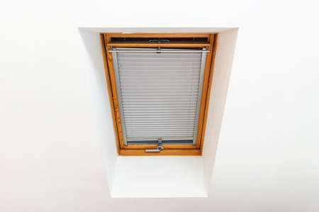 A window on a sloping wall under the roof of a house with white walls