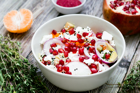 salad with fresh vegetables, feta cheese, garnets and tangerines. healthy diet or vegetarian food on a wooden background. Top view. Stock Photo