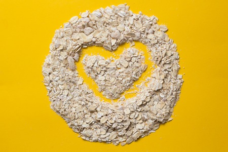 oatmeal flakes for health. vegetarian food for breakfast on a colored background. organic product. heart concept in a circle.