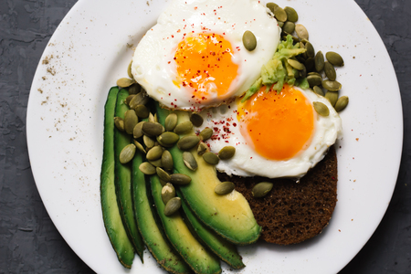 sandwich with fresh vegetables, avocado, hard-boiled eggs and pumpkin seeds with olive oil and bread. healthy diet or vegetarian food on a white background. salad with yolks on toast. top view