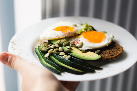 sandwich with fresh vegetables, avocado, hard-boiled eggs and pumpkin seeds with olive oil and bread. healthy diet or vegetarian food on a white background. salad with yolks on toast.