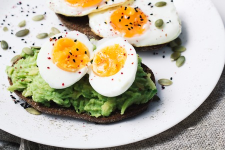 sandwich with fresh vegetables, avocado, hard-boiled eggs and pumpkin seeds with olive oil and bread. healthy diet or vegetarian food on a white background. salad with yolks on toast