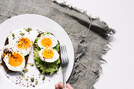 sandwich with fresh vegetables, avocado, hard-boiled eggs and pumpkin seeds with olive oil and bread. healthy diet or vegetarian food on a white background. salad with yolks on toast. top view.