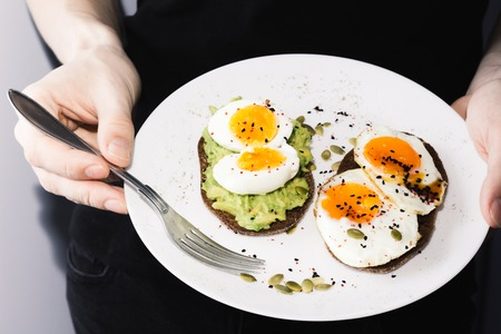sandwich with fresh vegetables, avocado, hard-boiled eggs and pumpkin seeds with olive oil and bread. healthy diet or vegetarian food on a white background. salad with yolks on toast in hands. Фото со стока