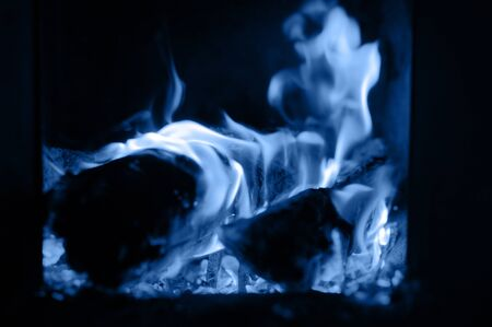blurred burning coals in the stove, tinted classic blue color trend 2020 year 版權商用圖片