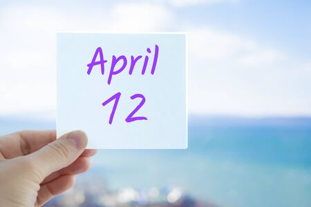 April 12th. Hand holding sticker with text April 12 on the blurred background of the sea and sky. Copy space for text. Spring month in calendar concept.