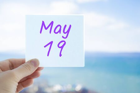 May 19th. Hand holding sticker with text May 19 on the blurred background of the sea and sky. Copy space for text. Month in calendar concept.