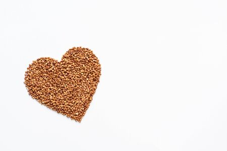 Heart from buckwheat isolated on white background. Top view. Concept of healthy food. Space for text