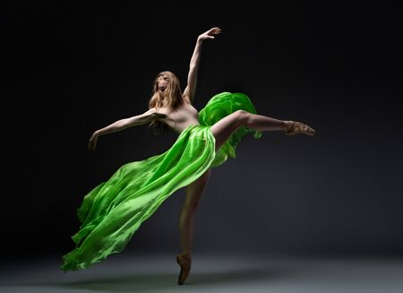 female ballet dancer in green skirt in wind movement 写真素材