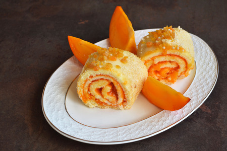 Jam filled Swiss Roll. Sweet sponge roll with persimmon jam on vintage porcelain plate. Teatime with Slices of sponge cake. It is delightfully yummy and perfect with a hot cup of tea.
