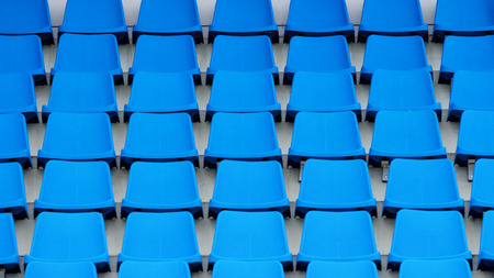 Empty plastic chairs in the stands of the stadium. Many empty seats for spectators in the stands. Empty plastic chairs seats for football fans. Stock Photo