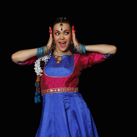 Girl dancer of Indian dances. A woman in an Indian suit. Portrait on a black background. Stock Photo